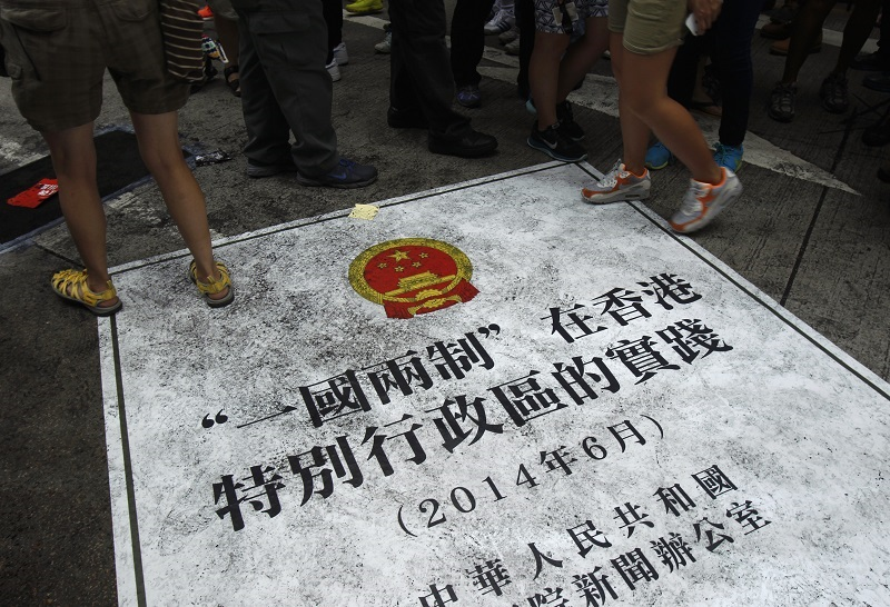 "People step on a sign depicting an enlarged cover of China's recent ""One country, two systems"" white paper during a mass protest demanding universal suffrage in Hong Kong"